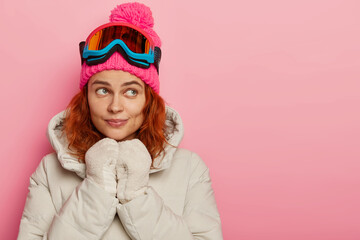 Papiers peints Glisse hiver Thoughtful feminine girl with ginger wavy hair wears warm hat, coat and gloves, thinks about going to snowy beach, uses protective snowboarding glasses, poses indoor against pink background.