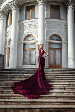 Beautiful slender girl in a dark red silk flowing dress with a long train on the steps of the palace.