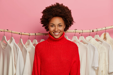 Happy dark skinned female stylist with Afro hairstyle, smiles broadly, wears knitted red sweater, stands near rack with hangers. Friendly shop assistant in fashion store, white clothes in background Wall mural