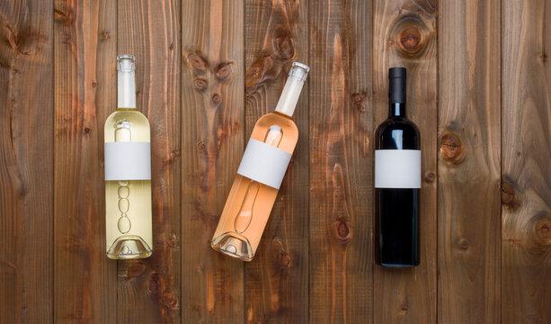 Bouteilles vin rosé rouge blanc fond bois clair pierres étiquettes