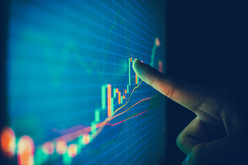 Closeup hand pointing finger on blue color monitor to analyze stock market graph