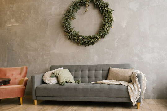 Gray sofa and a large Christmas wreath on the wall in the living room