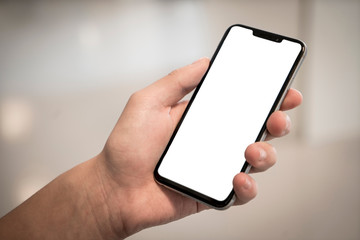 Closeup hand holding smartphone with blank white screen with copy space against natural light bokeh backdrop. Add your own content.