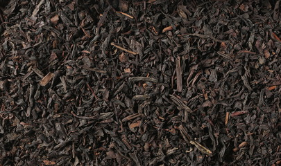 Dry black tea leaves background and texture