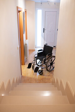 A wheelchair in front of a staircase in a house