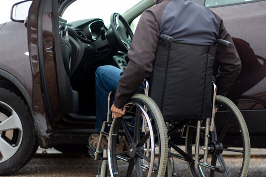 A man in a wheelchair trying to get into the driver's seat of a car