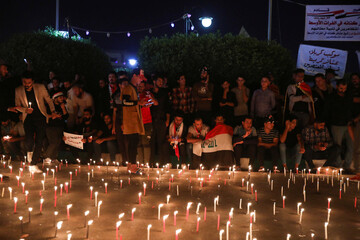 Demonstrators light up candles for the people killed at an anti-government protest in Iraq, in the holy city Kerbala
