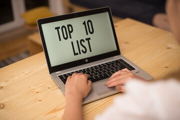 Writing note showing Top 10 List. Business concept for the ten most important or successful items in a particular list woman with laptop smartphone and office supplies technology