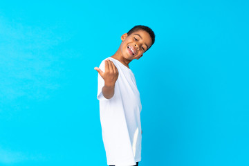 African American boy over isolated blue background inviting to come with hand. Happy that you came