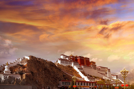 Lateral view of the Potala Palace in Lhasa, Tibet, against a colorful sunset sky covered by dramatic clouds.