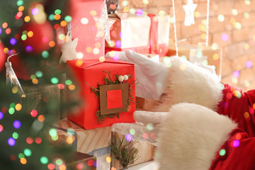 Santa Claus putting gift box on mantelpiece, closeup