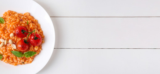 Plate with tasty risotto on wooden table with space for text