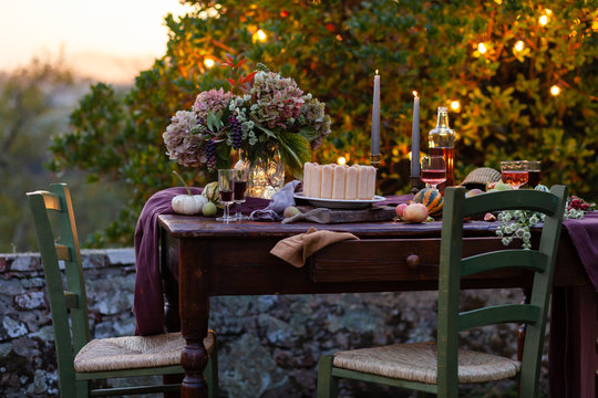 Beautiful and elegant table setting for a romantic date for a couple. Private terrace outside the restaurant. Lights on background