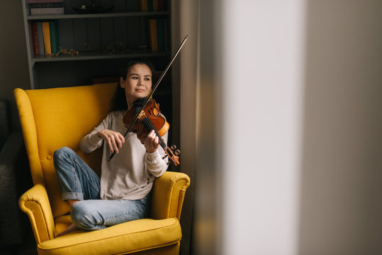 Fiddler plays tender music on a violin in her home near the window. Attractive young woman musician plays the violin sitting on soft chair.