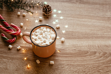 Christmas moody picture with pink cup of coffee with marshmallows and confetti