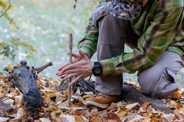 Man trying to start a fire in the wild using primitive method of friction. Practicing survival skills - Image