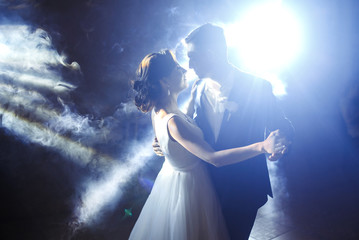 First wedding dance of newlywed. Wedding couple dancing in the darkness. Groom holds bride's hand dancing with her in the middle of a restaurant. Happy bride and groom and their first dance.  Fototapete
