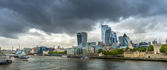 London skyline at cloudy day including skyscrapers at financial district. Picture took along the riverside. Wall mural