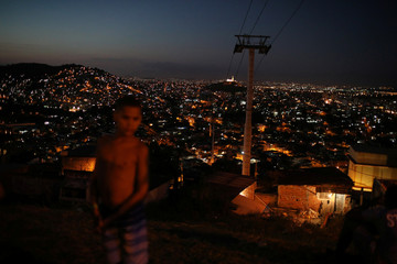 A boy waits for a kite during a demonstration called Kites for Peace, where one thousand white kites are released as a symbol of peace in the Complexo do Alemao slum, in Rio de Janeiro