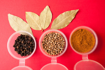Spices: black pepper, ground red pepper and coriander peas in jars and Bay leaf on a red background