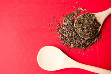 Spices: dried Basil grass on wooden boat on red background