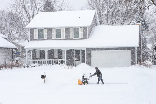 Man using a snowblower to clear his sidewalk and driveway