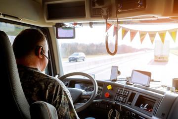 Driver in cabin of big modern truck Fotomurales