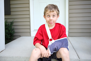 Funny boy with broken arm crossing his eyes and sticking his tongue out