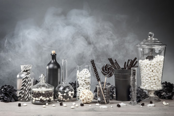 Black and White candy bar with smoke and glass jars and chemistry bottles