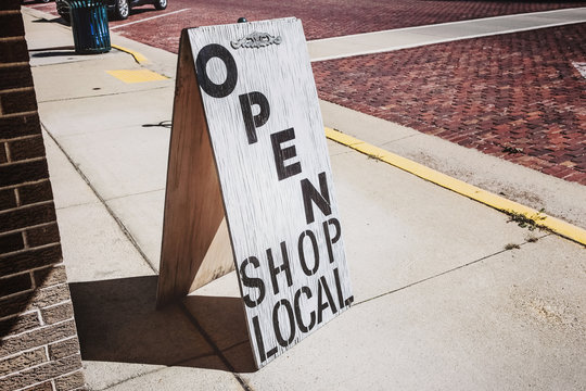 Open shop local sign on a wooden sandwich board outside of a store