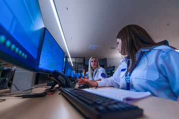 Female security operator working in a security  data control room offices