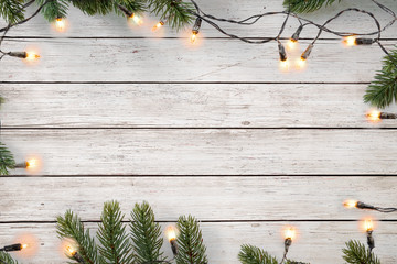 Christmas lights bulb and pine leaves decoration on white wood plank, frame border design. Merry Christmas and New Year holiday background. top view.