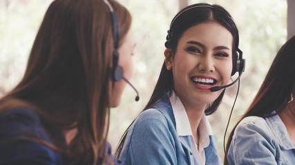 Customer support agent or call center with headset works on desktop computer while supporting the...