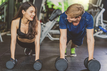 Couple young diversity working out in gym fitness sport complex, workout working out arms and cardio, posture position, Push up on weights,Doing plank on kettlebell. sports and healthcare concept