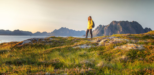Canvas Prints Honey Woman with a backpack looks at the fjord. Ocean and mountain sunset landscape. Scenic view. Travel, adventure Explore North Norway. Summer in Scandinavia