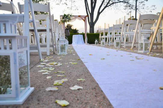 White cloth runner flanked by empty white chairs leading to a wedding altar