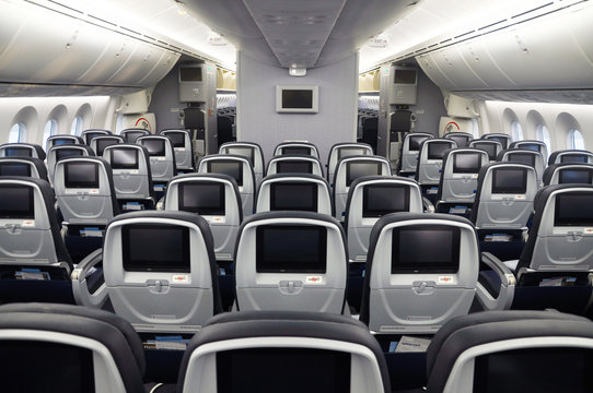 Empty commercial airplane seats viewed from the rear