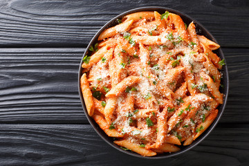 Penne alla Vodka is a classic Italian pasta dish made with penne in a creamy tomato and vodka sauce close-up in a plate. Horizontal top view