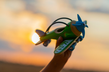 Boy's hand holds a wooden airplane against the sky during sunset. Close-up of a child's hand with a plane. Toy plane in the hand of a child of eight years. Freedom and happiness concept.