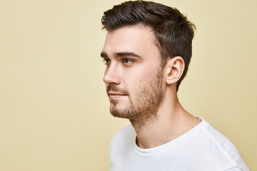 Half profile image of handsome young Caucasian man with good skin, brown eyes, black stylish hair and stubble posing isolated against blank studio wall background, looking in front of him, smiling