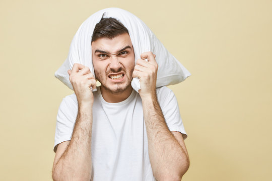 Insomnia man, sleep deprivation and sleeping problem concept. Depressed young man with beard covering ears and head, trying to block anooying loud alarm sound or awakened at night by noisy neighbour