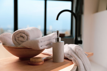 Clean towels, soap dispenser and shower brush in bathroom