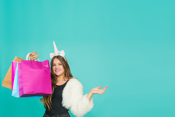 Portrait of a smiling pretty girl with shopping bags over blue background. Black friday concept. Kawaii teenage girl. Cute young woman with unicorn horn. Copy space.