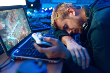 Male gamer sleeping at his laptop after challenge