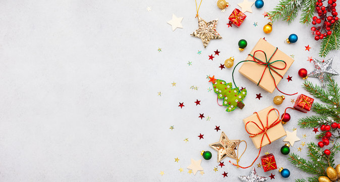 Christmas background with gift boxes, festive decor, fir tree branches and paper cards notes. Flat lay.
