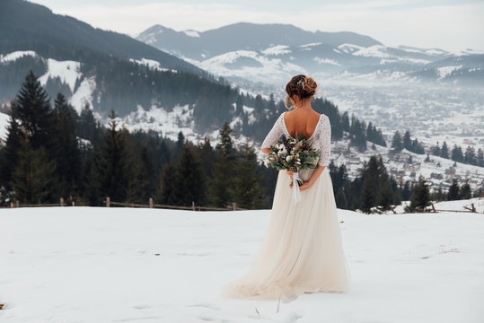 Bride in white wedding dress holding colorful flowers bouquet in hands and posing outdoors. Winter wedding and season floral concept. Mountains on background.