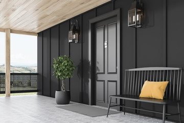 Black front door of black house, bench, side view