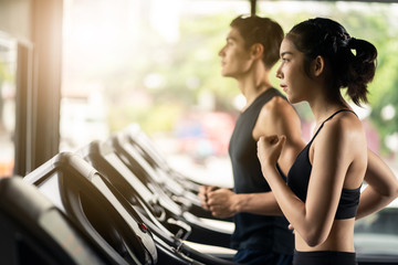 Young fit two friends of Caucasian man and Asian woman exercising and working out in gym. They jogging on treadmill or running machine, looking in front focus on training, healthy, wellness in fitness