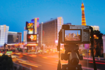 Set the digital camera on a tripod to record the light of the lights from the building and the lights of the cars in the city at twilight.