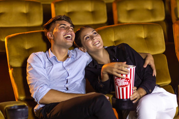 Young man laughing and hugging girlfriend with popcorn bucket while watching movie during couple date in movie theater